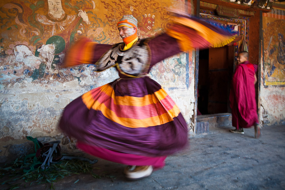 A dancer rehearses for the Tamshingphala dance festival in Bhutan, entertaining a passing monk.